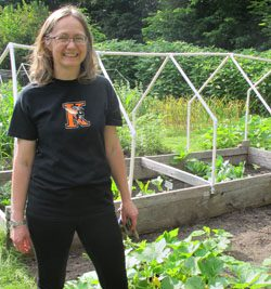 Staff member in front of a raised garden bed